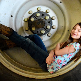 In the Tire by Tiffany Serijna - Babies & Children Child Portraits ( child, farm, little girl, girl, cowgirl, candid, fun, photo, tractor, smiling, portrait, tire )