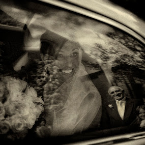 Bride is arriving in the car. Her father is looking at her by Kira Likhterova - Wedding Getting Ready