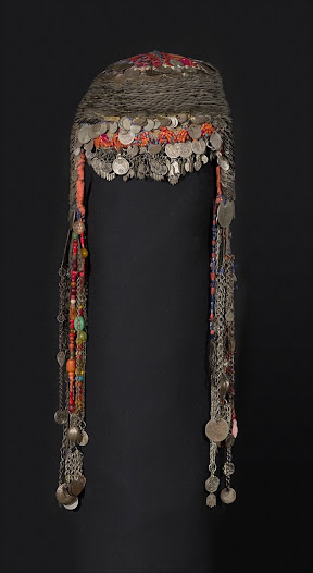 <b>Bridal headdress, 'wuqāyat al-darāhim', Samuʿa, Hebron Hills, southern Palestine, circa 1840s with later additions.</b>  The <i>wuqāyat al-darāhim</i> has densely packed rows of coins, beads, charms and pendants, which shielded the bride from the 'eye of envy' when she was most vulnerable – on procession to her new home and at her second public appearance, celebrating the consummation of the marriage.  These special ceremonial headdresses were usually family heirlooms, and were lent to families who did not own one for a few piastres or were returned filled with sweets.