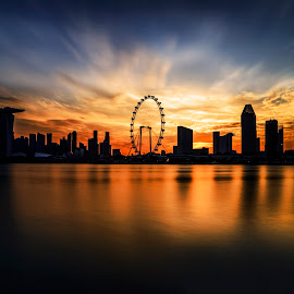 Blazing Sky by Gordon Koh - City,  Street & Park  Skylines ( clouds, shenton way, reflection, skyline, singapore icon, silhouette, marina bay sands, singapore, landmark, skyscraper, sunset, movement, asia, mbs, singapore flyer, long exposure, waterfront, golden hour, ferris wheel )
