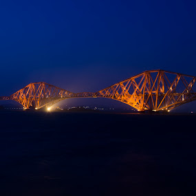 by Steven Stamford - Buildings & Architecture Bridges & Suspended Structures ( forth, old, firth, architecture, travel, transportation, long, historic, sky, forth bridge, train, structure, tourism, fife, landmark, cantilever, edinburgh, dawn, railway, view, bridge, shore, crossing, scotland, famous, queensferry, link, road, seaside, engineering, coast, iron, lights, transport, rail, forth rail bridge, water, uk, scottish, sea, scenic, steel, scottish scenic, urban, red, sunset, victorian, summer, night, historical, scenery, river, britain,  )
