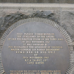 This plaque is located on the Melbourne Town Hall, Collins St, Melbourne, above the foundation stone. It reads: THIS PLAQUE COMMEMORATES THE CENTENARY OF THE LAYING OF THE FOUNDATION STONE OF THE ...