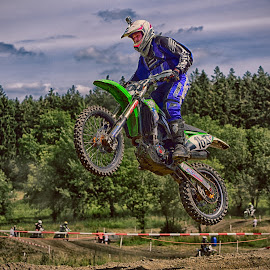 Landing Jumper by Marco Bertamé - Sports & Fitness Motorsports ( one hundred sixty-eight, green, forest, number, race, 168, jump, landing, motocross, blue, dust, cloudy, clumps, alone, competition )
