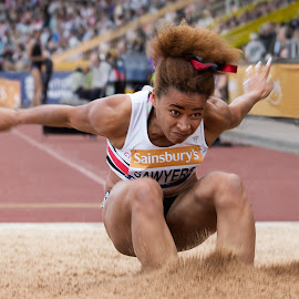 A soft landing.  by Ron Russell - Sports & Fitness Running ( splash down, sand, female, bad hair, long jump, long, athlete, leap )