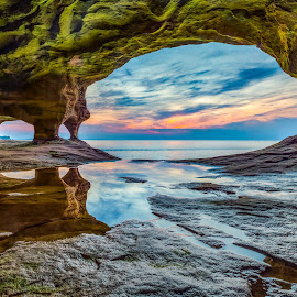 Superior Cavern by Kenneth Keifer - Landscapes Caves & Formations ( calm, reflection, setting sun, superior, colorful, rock, coastline, landscape, cave, sun, coast, tranquil, seacave, sky, nature, evening, water, cavern, munising, paradise point, christmas, sea, horizon, lake superior, grotto, lake, scenic, great lakes, seascape, dusk, alger county, sea cave, michigan, upper peninsula, sunset, hidden, sundown, secret, pictured rocks )