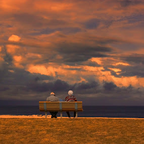 Enjoying the View by Dennis Granzow - People Couples ( senior citizens, park bench, storm clouds, seascape, lake erie )