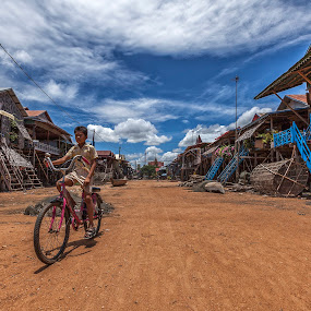 Ride By by Steve Badger - City,  Street & Park  Street Scenes ( village, asia, travel, cambodia, siem reap,  )