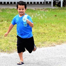 Grandson enjoying the bubbles by Priscilla Renda McDaniel - Babies & Children Children Candids ( bubble blower, having fun, running, boy, young )