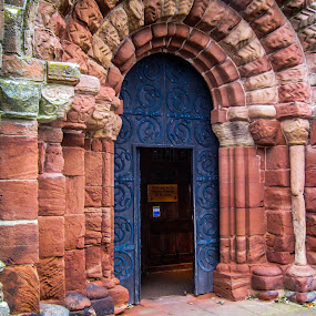 Door of the Priory Church by Del Candler - Buildings & Architecture Architectural Detail ( st. bees, church, blue, arches, door, stone,  )