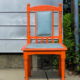 An orange chair by David Stone - Artistic Objects Furniture ( chair, orange, wooden chair, building wall, orange chair, sidewalk )