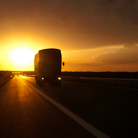 Truck traveling at sunset by Deyan Georgiev - Transportation Automobiles ( interstate, nobody, trailer, highway, truck, shipment, vehicle, driving, travel, transportation, road, landscape, cargo, sun, business, transporting, contrast, speeding, shipping, sky, perspective, industry, motion, lorry, clouds, orange, asphalt, moving, speed, horizon, motorway, trucking, front, scenic, wide, dusk, rural, country, diesel, sunset, outdoors, freight, summer, view, sunrise, delivery, fast, freeway )