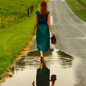 Walking in the Rain by Freda Nichols - People Street & Candids ( water, girl, woman, road, puddle, rain, , Spring, springtime, outdoors, path, nature, landscape )