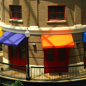 View from Across the Street by Elizabeth Stein - City,  Street & Park  Street Scenes ( red doors, orange, blue, door, awnings, yellow, lightposts )