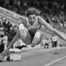 The Jumper.  by Ron Russell - Sports & Fitness Other Sports ( winning, athletics, gold medal, jumping, black and white, mono, women, running, championships )