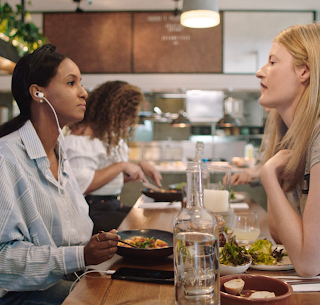 Two women having a conversation while eating food.