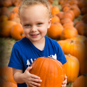 I Can Hold My Pumpkin Now by Bonnie Davidson - Babies & Children Child Portraits ( child, pose, orange, blonde, pumpkin patch, curles, blue, hands, smile, boy, portrait, eyes,  )