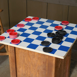 Checkers anyone? by Priscilla Renda McDaniel - Artistic Objects Toys ( red disc, blue squares, white squares, chair, black disc, checkers, game, board )