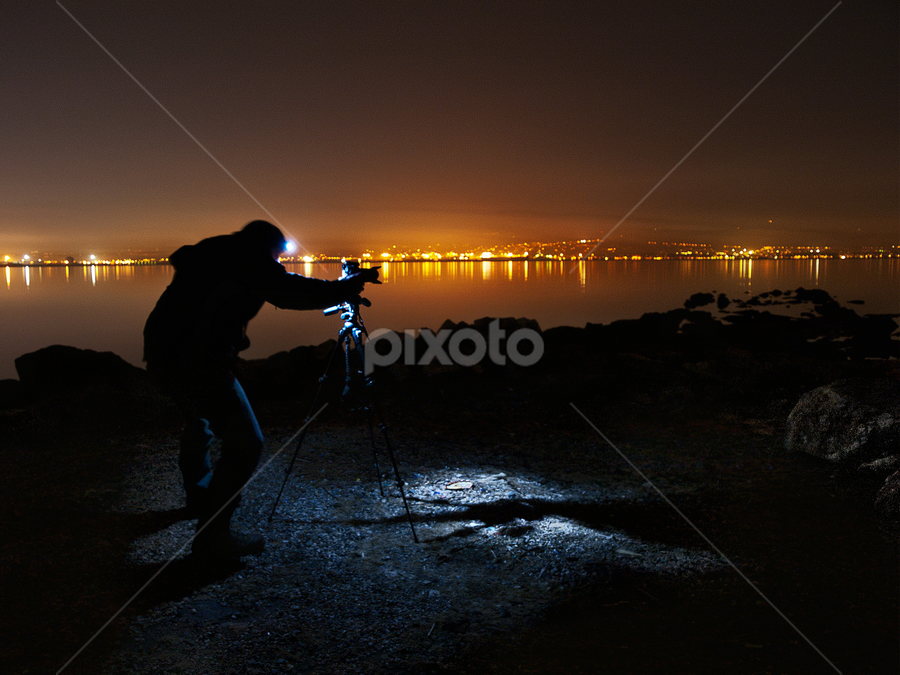 setting up the camera by Paschalis Angelopoulos - Professional People Business People ( night panorama, thessaloniki bay, settings, photographer, city lights, tripod, , photographers, taking a photo, photographing, photographers taking a photo, snapping a shot )