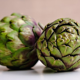 Pair of artichoke by Cynthia Linderbeck - Food & Drink Fruits & Vegetables ( isolated, studio shot, purple, green, side view, white background, crop, isolated objects, organic, artichoke, color image, color, no people, food, healthy eating, dietary fiber, fruits and vegetables, freshness, vegetable, raw food )