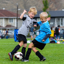 Close Encounters on the Soccer Pitch by Garry Dosa - Sports & Fitness Soccer/Association football ( tournament, ball, blue, outdoors, boys, movement, sports, action, children, grey, game, people, soccer )