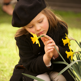 Sad young girl in beret stroking daffodil by Nick Dale - Babies & Children Child Portraits ( trousers, lawn, grass, daffodil, narcissus, leaves, spring, pretty, stalks, portrait, child, blonde, girl, stroking, nature, overcoat, brown, beret, stems, flowers, garden, coat, jonquil )