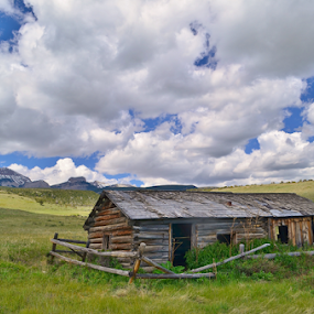 Cut Across Cabin by Don Evjen - Buildings & Architecture Decaying & Abandoned ( clouds, cabin, mountains, barn, montana, blue skies, rail fence, rustic, spring, green grass )