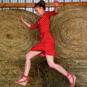 Jumping Hay Bails by Freda Nichols - People Portraits of Women ( barn, jumping, woman, hay, bails, red dress, , women, lady, red )