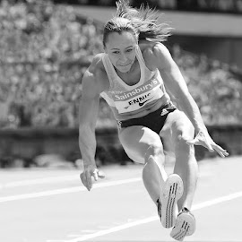 Jess Ennis, going for Gold.  by Ron Russell - Sports & Fitness Running ( spotr, sand, ladies, athletics, jumping, black and white, jess, shadows, flight, london, female, in mid flight, olympic stadium, long jump, mono, athlete )