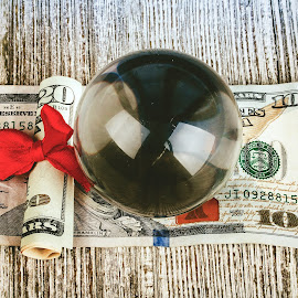 Different way to view money by Rob Heber - Artistic Objects Other Objects ( greed, reflection, detail, gift, smooth, crystal ball, wood, still life, red ribbon, indoors, wood grain background, rolled bill, ribbon, glass, money, objects, wood grain, closeup, abstract, ideas, studio lighting, red bow, studio shot, glass orb, texture, glass ball, gift wrapped, close up, twenty dollar bill, concepts, reflecting, glass sphere, rough texture, paper money, cash, finance, bow, conceptual, hundred dollar bill, overhead view )