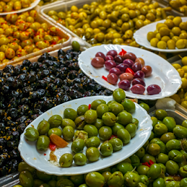 A variety of types of olives at a market stall by Roberto Sorin - Food & Drink Fruits & Vegetables ( london, gourmet, sign, cork, sauce, view, olive, english, portobello, different, vibrant, natural, barrels, gastronomy, stall, brown, ancient, delicious, market, notting, nutrition, closeup, tasty, colorful, color, yellow, tourism, dried, interior, supermarket, oil, variety, eat, close, organic, barrel, types, famous, green, black, cuisine, health, food, meal, outdoor, hill, sale, olives, healthy, wooden, fresh, travel, ireland,  )