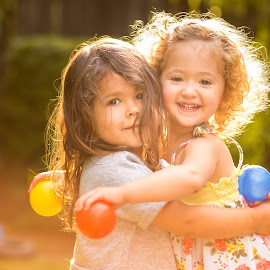 Girlfriends by Mike DeMicco - Babies & Children Child Portraits ( girls, hug, colorful, girlfriends, children, fun, kids, cute, pretty, portrait, playing, love, girl, sweet, happy, light, outside )
