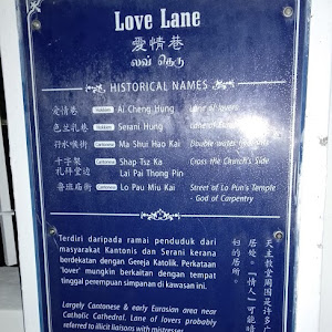 Plaque on one edge of a narrow street in the area of the city Georgetown in Penang, Malaysia, one of the most cheap touristy places to get a beer in the city. English portion says: