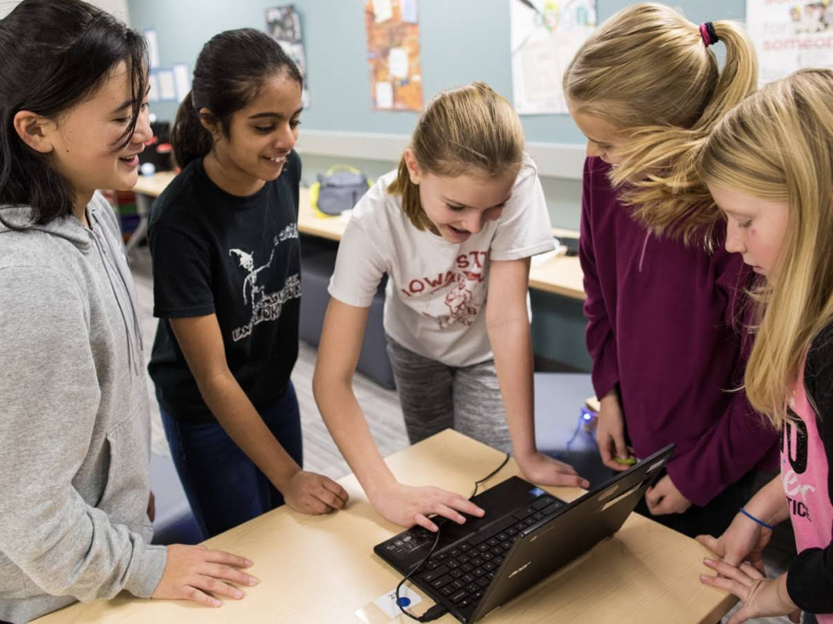 Four Girls watching a Laptop, laughing on a Classroom