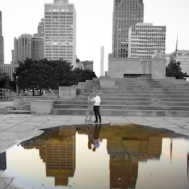 Reflection in a puddle by Justin Duff - Buildings & Architecture Other Exteriors ( reflection, selective color, holding, sunset, artistic, couple, architecture, detroit, engagement, city )