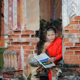 Neophyte reading a book in Temple . by Visoot Uthairam - People Portraits of Men ( reading, person, single, street, buddhist, cultural, little, rustic, people, asian, child, religion, candle, happy, southeast, tradition, abstract, belief, poor, traditional, young, portrait, buddha, rural, neophyte, temple, outdoor, background, book, summer, atmospheric, religious )