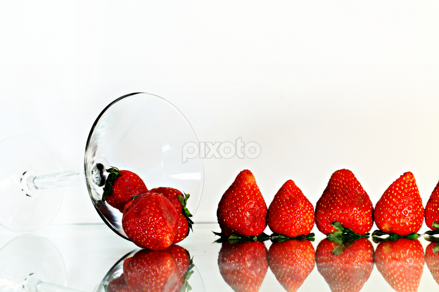Strawberries dropping from a glass. by Dipali S - Food & Drink Fruits & Vegetables ( fruit, red, food, glass, white, health, strawberry, pwc87, row,  )