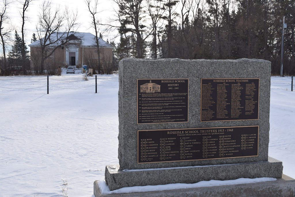 This plaque is located in front of the Roseisle School building. There is a bench in front of the plaque for sitting and reflecting. Transcription: 1892 The R.M. of Dufferin responded to a ...