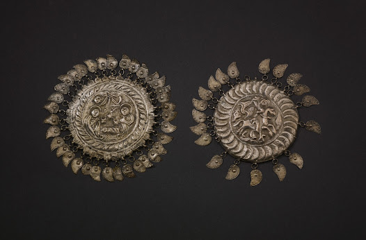 These hammered silver alloy discs were sewn to the top of a woman's fez-like cap to ward off the evil eye. They are a Muslim form, however, both are decorated with Christian subjects: the Nativity, and St George and the Dragon. St George's Day in April was celebrated throughout the Balkans. The name tepeluk (singular) comes from the Turkish tepé (hill) because the discs are usually domed.