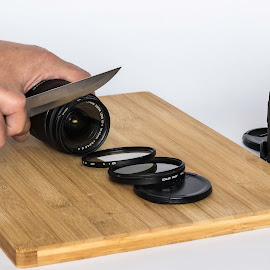 Slicing the lens by Chris Allen - Artistic Objects Still Life ( slicing vegs, hands, camera, chopping board, lens, knife )