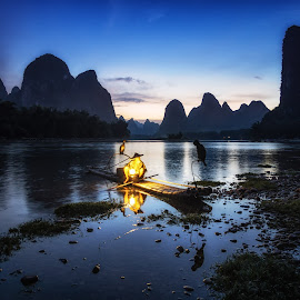 Cormorant Fisherman at Night by Aaron Choi - Landscapes Waterscapes ( limestone, hills, bamboo, mountain, li river, karst, travel, landscape, xingping, chinese, asian, lantern, mountains, nature, asia, old man, light, man, bamboo boat, china, cormorant, beautiful, magnificient, tourism, blue hours, boat, riverbank, bird, yangshuo, sunset, night, fishing, raft, fisherman, river )