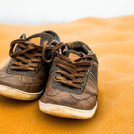 A pair of brown shoes in the desert by Péter Mocsonoky - Artistic Objects Clothing & Accessories ( walking, pair, foot, dune, travel, recreation, run, adventure, nature, dubai, sunny, shoe, alone, shoes, sand, extreme, desert, dry, journey, red, outdoor, active, hot, summer, sahara, brown, sneakers, walk )