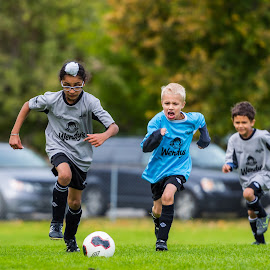 Chasing the Ball by Garry Dosa - Sports & Fitness Soccer/Association football ( tournament, blue, outdoors, boys, movement, sports, action, children, grey, game, people, soccer )