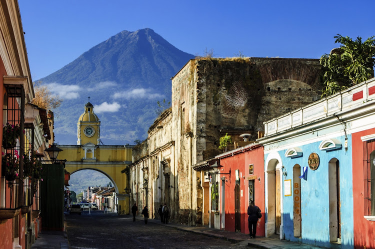 Antigua's famous cobblestoned street lined with painted shops, restaurants and hotels. Agua volcano looms behind Santa Catalina Arch, a landmark in this Spanish colonial town & UNESCO World Heritage Site.