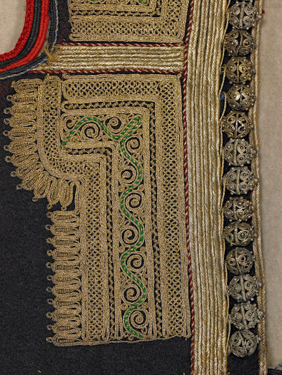 The woman's costume traditionally has one hundred silver filigree buttons. In this costume there is one row with twenty on the jacket and two rows with twenty buttons each on both the inner waistcoat and the longer outer coat. The five rows of buttons are visible in the image of the complete costume.
