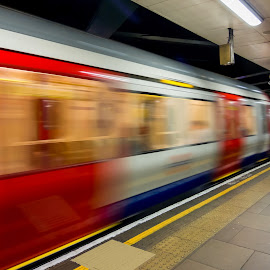 The Tube Departs by Jan Murphy - Transportation Trains ( walking stick, tube, way out, yellow, people, lights, district line, squares, movement, action, dirty, glass, train, motion, paving slabs, white, coats, sign, railings, red, london, tower hill, underground, fast, bags,  )