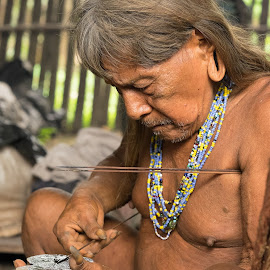 Huaroni man puts poison on blow darts by Alan Cline - People Portraits of Men ( huaroni, ecuador, indigenous, tribal, rainforest, amazon )