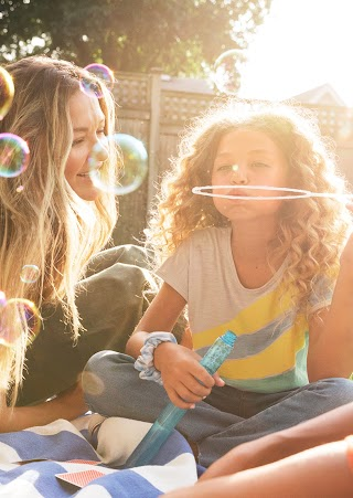 Three people sitting on a lawn and blowing bubbles.