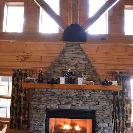 Fire in the Place by Thomas Shaw - Buildings & Architecture Architectural Detail ( mountain view, cabin, wood, logs, wood floor, stone, windows, rock, gray, stone fireplace, fire, mountains, curtains, floor, window, bears, glass, beam, brown, stones, place, fireplace, black )