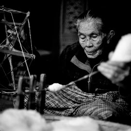 Old lady and her spinngingwheel by Indrawan Ekomurtomo - Black & White Portraits & People