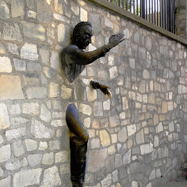 Whimsical Statue in Paris by Dee Haun - Buildings & Architecture Statues & Monuments ( exiting wall, paris, partial man, statue, park, man in wall, france, street scene, architecture, man )
